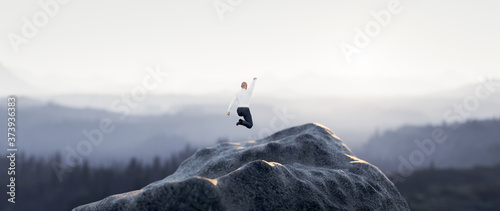 Fototapeta Businessman jumping for joy on the mountain. Success