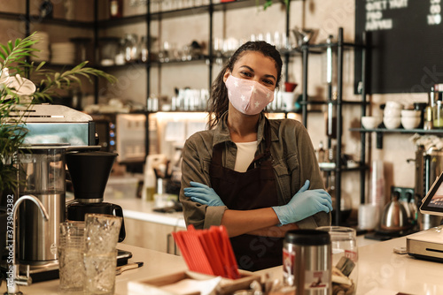 Fotografiet Woman with face mask standing at the counter