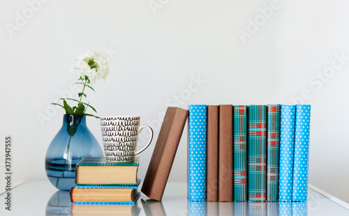 Foto Cozy home interior decor: stack of books and vase with white flower on a glass table