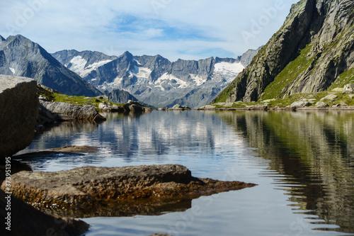 Fototapeta Bergsee mit Spiegelung eines Gebirges im Hintergrund in Tirol Österreich