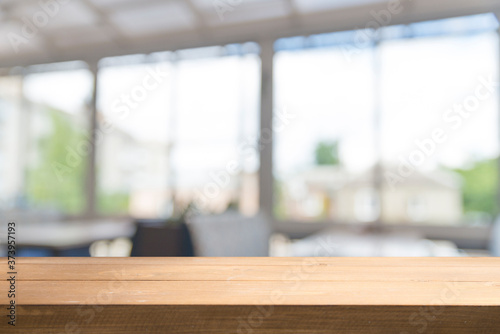 Obraz Wooden table on defocuced window with curtain background - fototapety do salonu