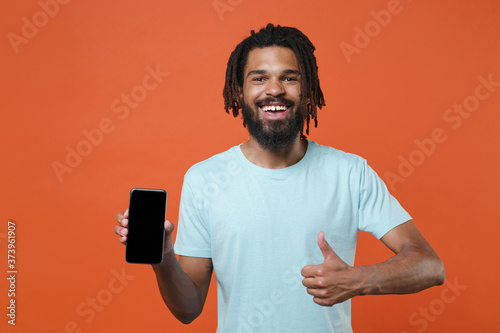 Obraz Funny young african american man guy in blue casual t-shirt isolated on orange background. People lifestyle concept. Mock up copy space. Hold mobile phone with blank empty screen, showing thumb up. - fototapety do salonu