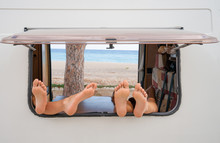Window Of A Camper Van. In The Window There Are Four Legs