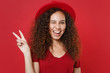 Blinking young african american woman girl in casual t-shirt hat posing isolated on bright red background studio portrait. People emotions lifestyle concept. Mock up copy space. Showing victory sign.