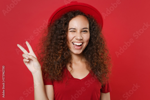Obraz Blinking young african american woman girl in casual t-shirt hat posing isolated on bright red background studio portrait. People emotions lifestyle concept. Mock up copy space. Showing victory sign. - fototapety do salonu