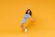 Full length portrait of cheerful young african american woman girl in denim clothes isolated on yellow background. People lifestyle concept. Mock up copy space. Dancing standing on toes, rising hands.