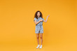 Full length portrait of surprised young african american woman girl in denim clothes isolated on yellow background studio portrait. People emotions lifestyle concept. Pointing index fingers aside.