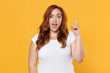 canvas print picture - Excited young redhead plus size body positive female woman girl 20s in white blank design casual t-shirt hold index finger up with great new idea isolated on yellow color background studio portrait.