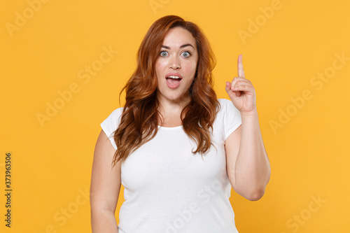 Fotografia Excited young redhead plus size body positive female woman girl 20s in white blank design casual t-shirt hold index finger up with great new idea isolated on yellow color background studio portrait