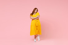 Full Length Portrait Pretty Smiling Beautiful Young Redhead Plus Size Body Positive Female Woman Girl 20s In Yellow Dress Posing Holding Hands Crossed Isolated On Pastel Pink Color Background Studio.