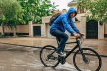 Full-length Outdoor Shot Of Handsome Man Cycling On His Bike Down The Street Next To The House. Male Courier With Curly Hair In Blue Raincoat Delivers Parcel Cycling With A Bicycle On A Rainy Day.