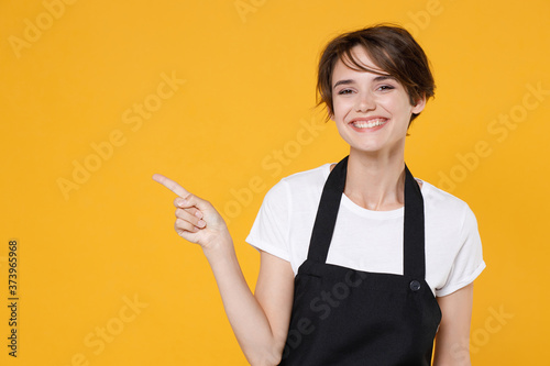 Stampa su Tela Smiling young female woman 20s barista bartender barman employee in white casual t-shirt apron pointing index finger aside on mock up copy space isolated on yellow color background studio portrait
