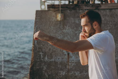 Obraz Portrait side view of handsome attractive young athletic boxer man guy 20s in casual white t-shirt black shorts posing training doing boxing exercises looking aside at sunrise over the sea outdoors. - fototapety do salonu