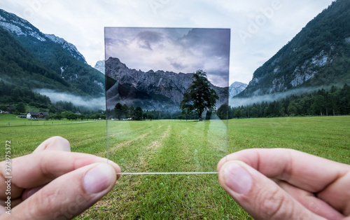 Cuadros en Lienzo Professional photographer holding ND Gradient Filter glass appreciating an effect