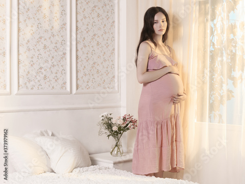 Young pregnant woman in home interior
