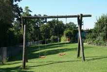 Wooden Swing With Red Seats For Children In Colony Of Allotment Gardens In The Vicinity Of Towns And Biggest Villages In Switzerland During Sunny, Summer Day Under Blue Sky.