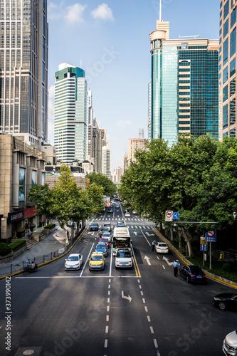 Photo Perspectiva de calle en gran ciudad con tráfico y árboles y rascacielos al fondo generando un punto de fuga