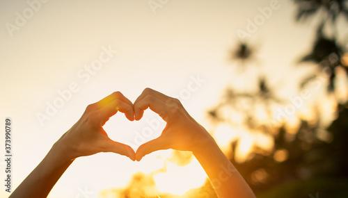 Foto Hand making heart shape on beautiful sunset background.