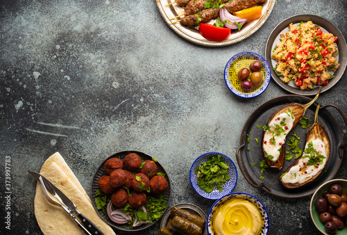 Slika na platnu Middle eastern or Mediterranean dinner with grilled kebab, falafel, roasted and fresh vegetables, assorted Arabic meze and appetizers on rustic background table