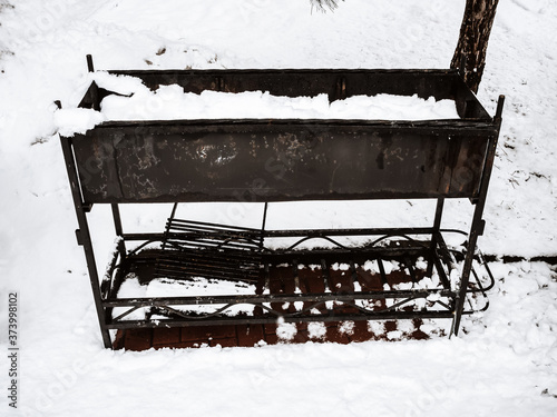 Iron black brazier stands covered with snow. Canvas Print