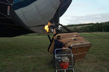Inflating A Balloon Lying On The Grass With Burning Air. A Fire Burning Inside The Ball