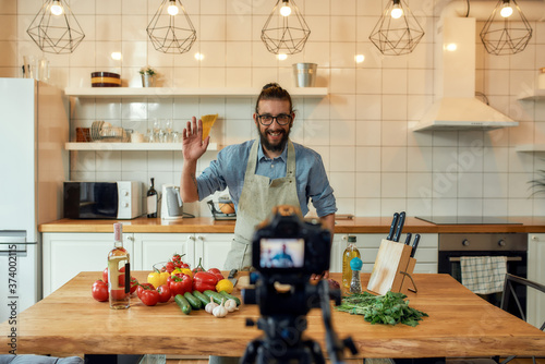 Young man, Italian cook in apron waving at camera, greeting audience, filming hi Canvas