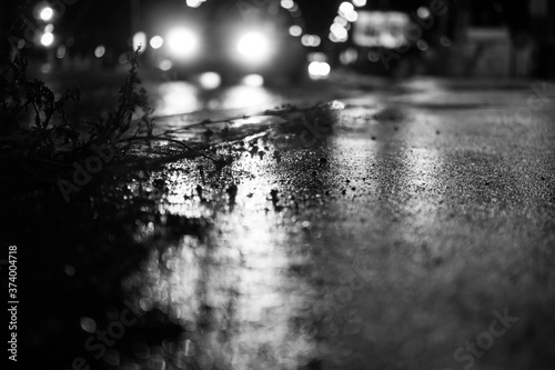 Foto Lights and shadows on wet road at rainy night.
