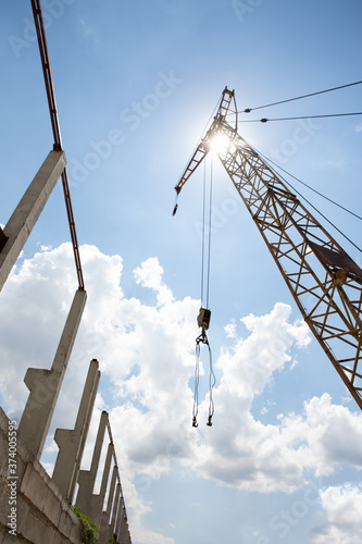 Photo Large construction crane on the background of a Sunny sky next to a building und