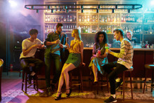 Gathering Place. Full Length Shot Of Young Men Drinking Cocktail At The Bar Counter And Flirting With Women They Just Met. Young Adults Having Drinks While Chatting At The Night Club
