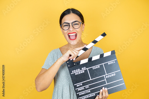 Fototapeta Young beautiful woman wearing glasses standing over isolated yellow background h