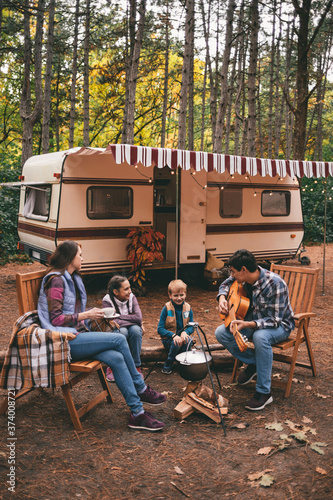 Fotomural Happy family on a camping trip relaxing in the autumn forest