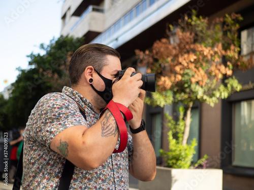 Fotógrafo hombre joven con tatuajes tomando una foto en una calle con edificios Fotobehang