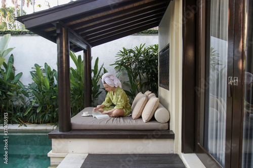 Fotografering Young caucasian woman in robe and hair wrapped in towel sitting at home and reading a book