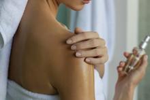 Woman Applying Body Oil To Moi...