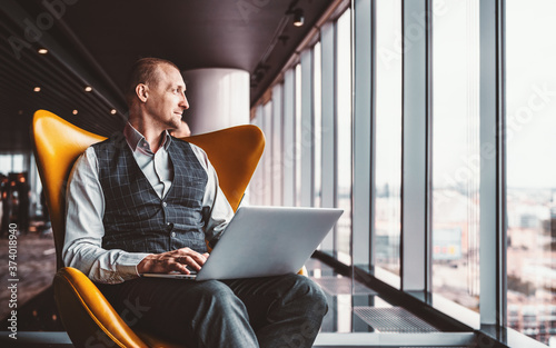 A handsome cheerful caucasian man entrepreneur is sitting with a laptop on his k Fototapeta