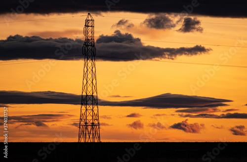 gran antena de trasmision en contraste al atardecer anaranjado con nubes negras Canvas