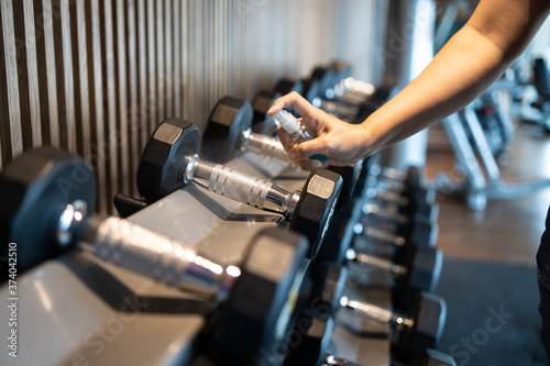 Fototapeta premium Hand of asian woman spraying alcohol into a dumbbell to clean it,prevent Coronavirus,safety of the COVID-19 outbreak,people cleaning of sport equipments with disinfecting spray in the gym or fitness