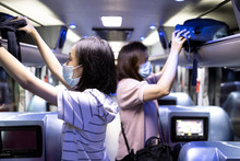 Asian Passenger Stowed Her Backpacks In A Overhead Storage On The Tour Bus,people Wearing Protective Masks To Safety From The Coronavirus,vacation Travel Trip In New Normal Conditions Under COVID-19