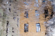 Vintage House Windows Reflected In A Muddy Puddle