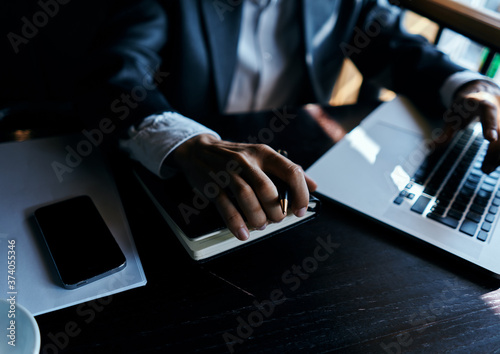 Obraz na plátně A business man in a suit is sitting in a cafe or with a laptop the work is an of