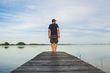 Man In Short Cargo Pants Standing On Wooden Pier And Observing The Surface Of Lake, Varazdin Lake, Croatia