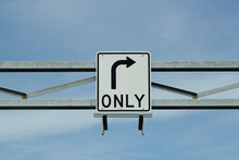 Right Turn Only Sign Against Blue Sky And Clouds.