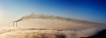Panoramic View Of Tops Of Three Smoking Stacks Of Thermal Power Station On The Horizon Taken From The Hill, Pipes In Morning Fog On Blue Sky, Concept Of Energy Generation, Ecology And Pollution