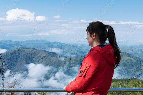 Fototapeta A young woman in a red jacket admires the mountains and clouds from above, the view from the back