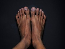 Close-up Male Feet Isolated On Black Background