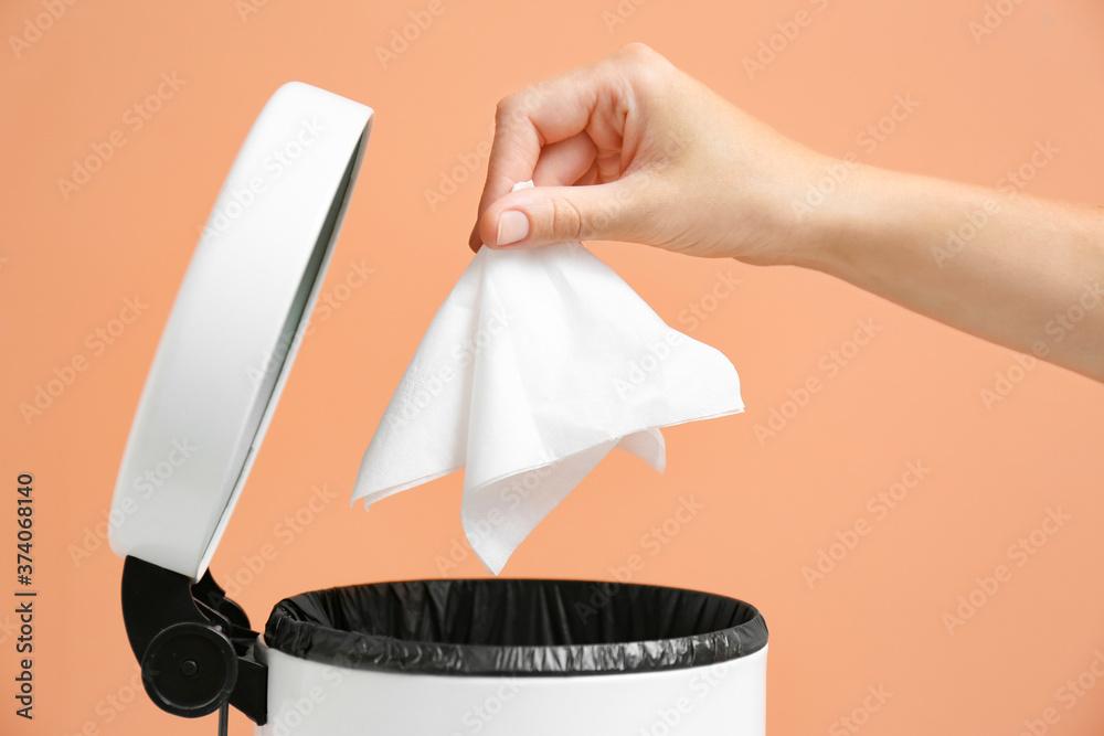Fototapeta Woman putting paper tissue into trash bin on light brown background, closeup