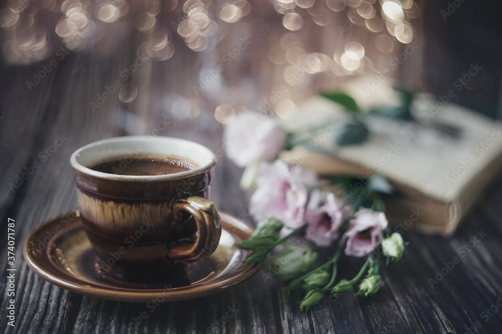 Fototapeta Cup of coffee, book and flowers on a wooden table. Background. Vintage. Postcard.