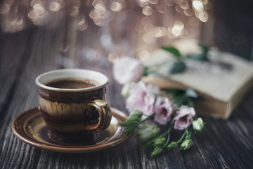 Cup of coffee, book and flowers on a wooden table. Background. Vintage. Postcard.