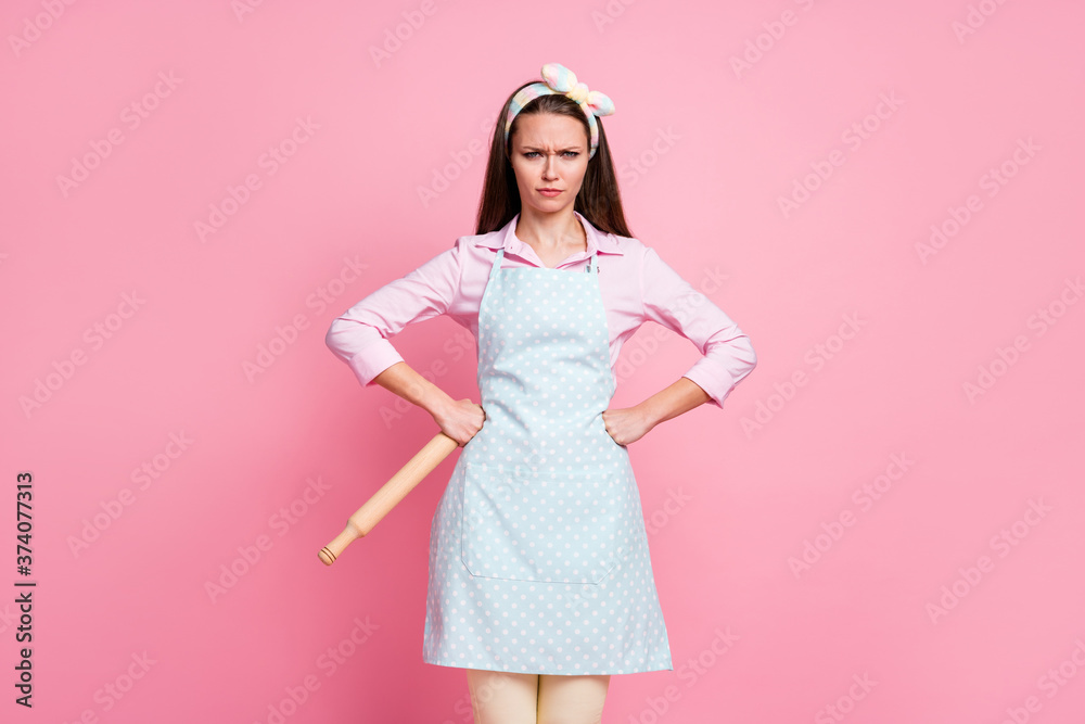Fototapeta Portrait of frowning aggressive mother wife hold rolling pin put hands waist want start scandal wear stylish trendy clothes isolated pastel color background