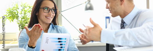 Businessman and businesswoman are sitting at table in office having dialogue Canvas